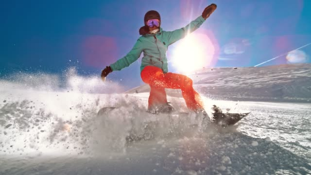 speed ramp female snowboarder causing a powder splash in sunshine - snowboard video stock e b–roll