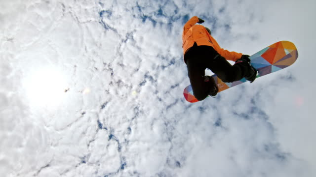 speed ramp female snowboarder grabbing her snowboard while in the air - sport video stock e b–roll
