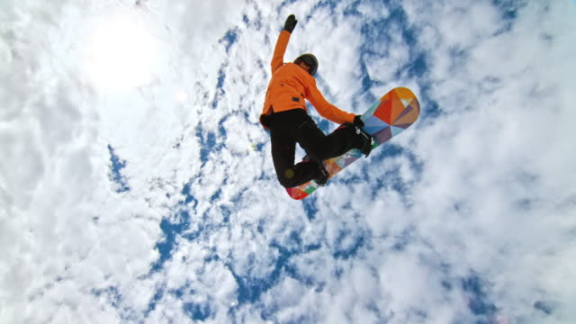 speed ramp female snowboarder grabbing her snowboard while riding in half-pipe - snowboard video stock e b–roll