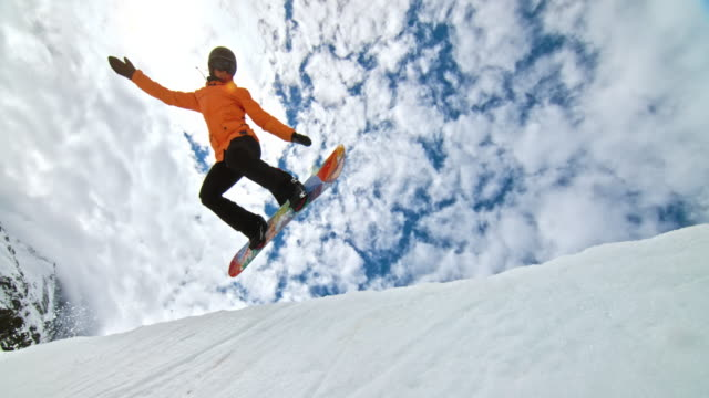 slo mo female snowboarder jumping in the half-pipe - snowboard video stock e b–roll