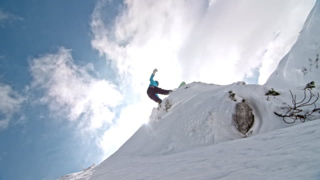 slo mo female snowboarder jumping off a rock into powder - snowboard video stock e b–roll