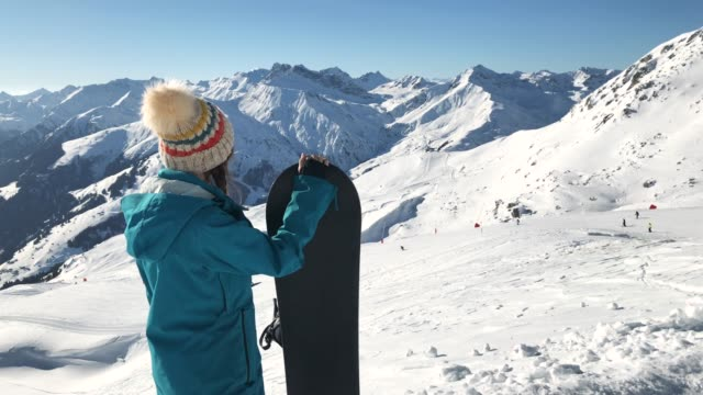 female snowboarder looking at the ski slope - snowboard video stock e b–roll