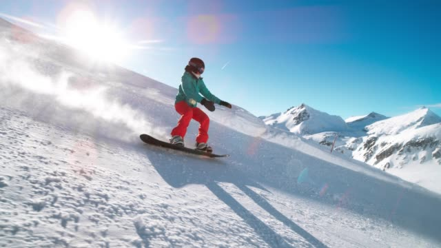 slo mo ts female snowboarder riding down the sunny mountain slope covered in fresh powder - snowboard video stock e b–roll