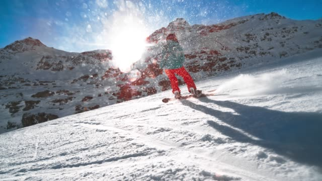slo mo ts female snowboarder riding on a slope with the sun shining behind the mountain - snowboard video stock e b–roll