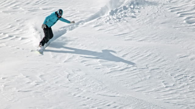 vídeos y material grabado en eventos de stock de slo mo female snowboarder riding powder snow - snowboard