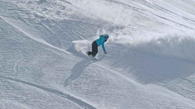SLO MO Female snowboarder riding sunny slope in powder snow
