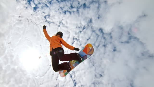 slo mo female snowboarder riding the half-pipe and jumping into the air - arms outstretched stock videos and b-roll footage