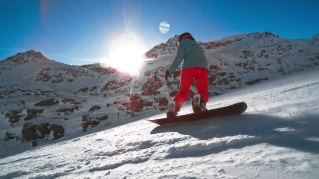 slo mo ts female snowboarder riding the sunny slope high in the mountains - sports equipment stock videos & royalty-free footage