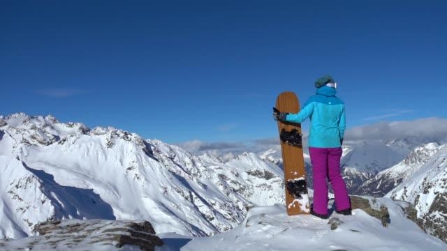 weiblicher snowboarder auf dem berg - wintersport stock-videos und b-roll-filmmaterial