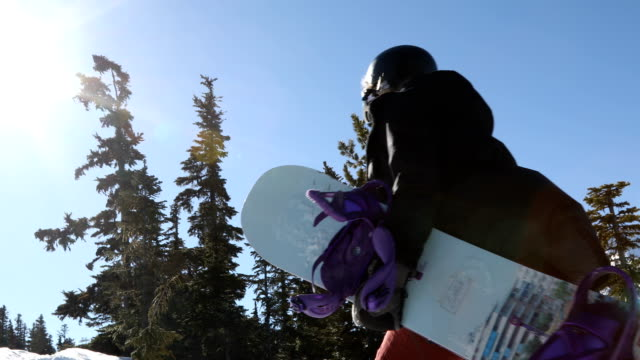 female snowboarder takes a moment on sunny mountain top - sports helmet stock videos & royalty-free footage