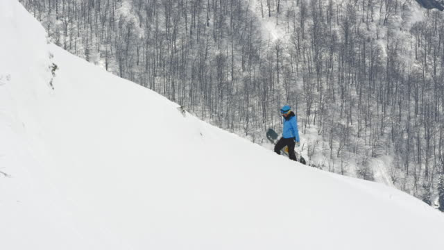 SLO MO Female snowboarder walking uphill in powder snow
