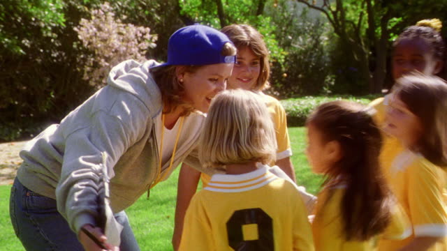 female soccer coach in baseball cap hugging her girls soccer team outdoors - baseball cap stock videos & royalty-free footage