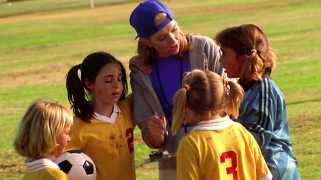 ms pan female soccer coach instructing girls on soccer team + leading them in cheer - blonde hair stock videos & royalty-free footage