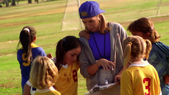 MS PAN female soccer coach instructing girls on soccer team + pointing to clipboard