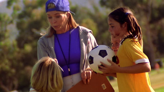 CANTED MS female soccer coach instructing three girls in uniforms outdoors / one girl holds ball