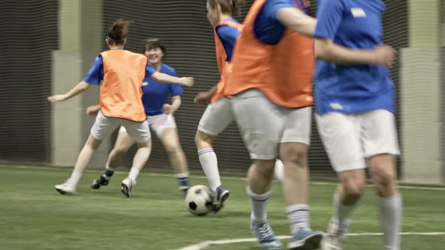 Female soccer player dribbling ball and scoring goal
