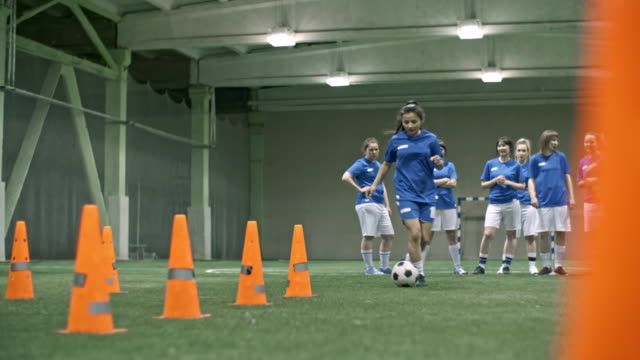 stockvideo's en b-roll-footage met female soccer player dribbling ball between orange cones - tienermeisjes