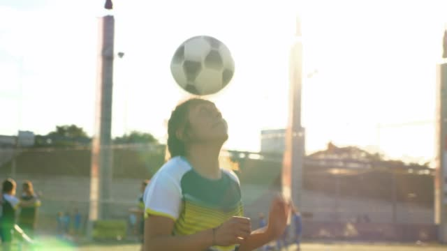 TS Female soccer player dribbling soccer ball with head before game