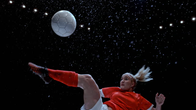 stockvideo's en b-roll-footage met slo mo female soccer player executing the overhead kick on rainy field at night - schoppen lichaamsbeweging