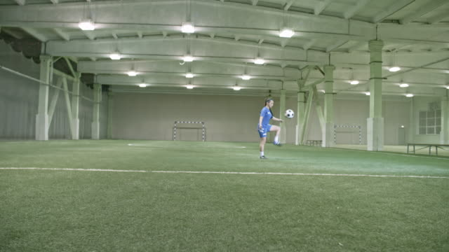 female soccer player juggling ball in empty indoor field - jonglieren stock-videos und b-roll-filmmaterial