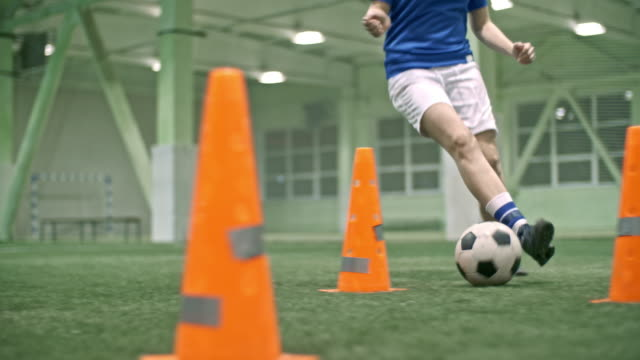 Female soccer player learning to dribble ball between cones