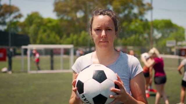 vídeos de stock e filmes b-roll de female soccer player standing on soccer field and holding ball in his arm - campo desportivo