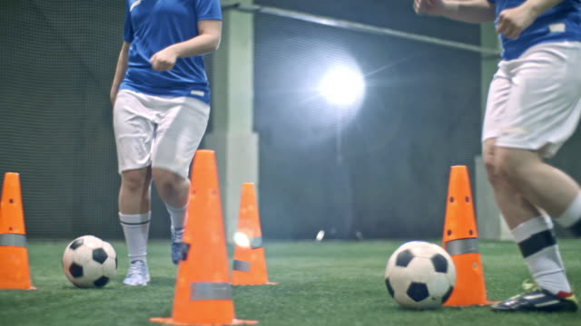 female soccer players competing in dribbling ball between orange cones - indoor soccer stock videos & royalty-free footage