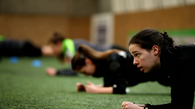 female soccer players doing plank exercise on a soccer field - football team stock videos & royalty-free footage