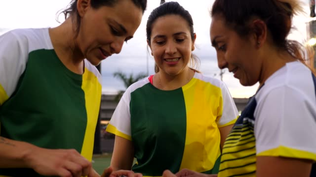 MS Female soccer players looking at smart phone after game
