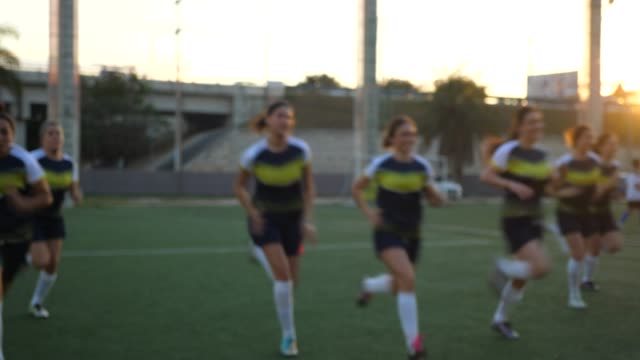 ms female soccer players running drills while warming up on field - practising stock videos & royalty-free footage