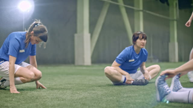 female soccer players stretching and joking in indoor field - strength stock videos & royalty-free footage