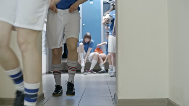 Female soccer team getting dressed in locker room