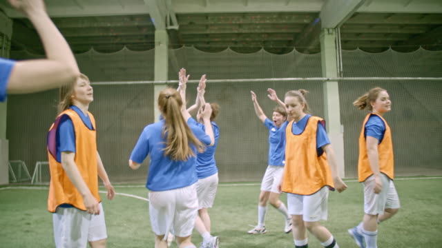 Female soccer team in blue winning friendly match and hugging