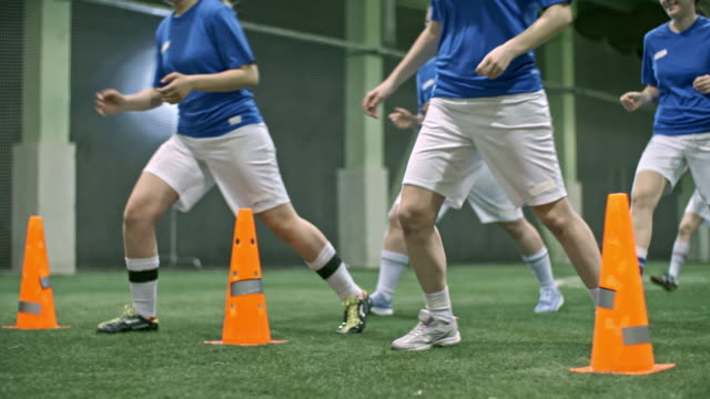 stockvideo's en b-roll-footage met female soccer team performing drills in indoor field - atlete