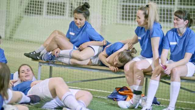 Female soccer team relaxing after practice in indoor field