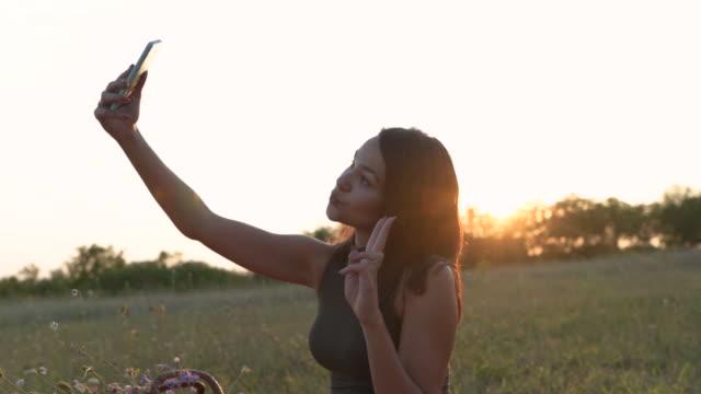 自然の中でセルフを撮る女性のソーシャルメディアのインフルエンサー - 口を尖らせる点の映像素材/bロール