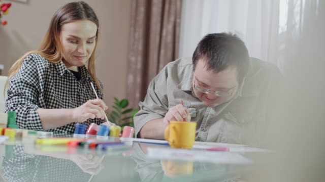 Female social worker and man with Down syndrome painting picture together