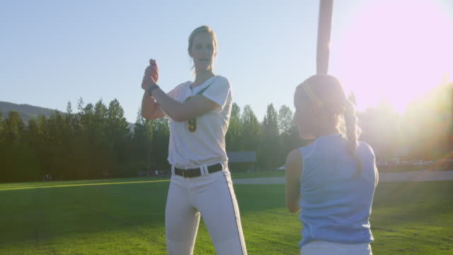 MS SLO MO Female softball player sharing batting technique with younger female players on field on summer evening