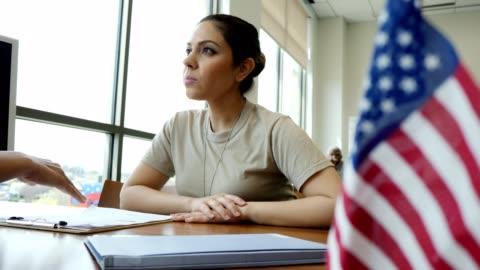 vídeos y material grabado en eventos de stock de mujer soldado escucha atentamente como agente de préstamos revisa la solicitud de préstamo - soldado ejército de tierra