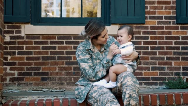 female soldier comforts her crying baby girl - veranda stock videos & royalty-free footage