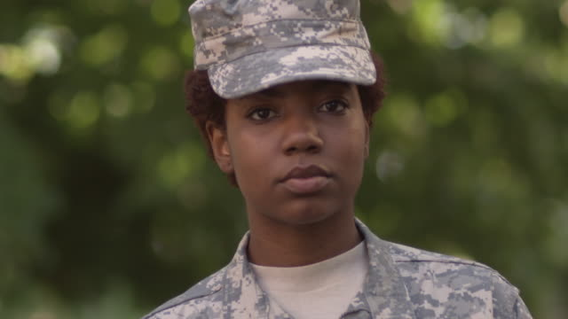 SM CU PORTRAIT Female soldier in cap profile turning to stare into camera/ Chicago, IL
