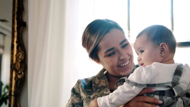 vídeos de stock e filmes b-roll de female soldier is reunited with her baby daughter - latino americano