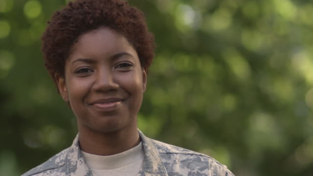 sm cu portrait female soldier looking up to stare into camera and break into a smile/ chicago, il - military stock videos & royalty-free footage