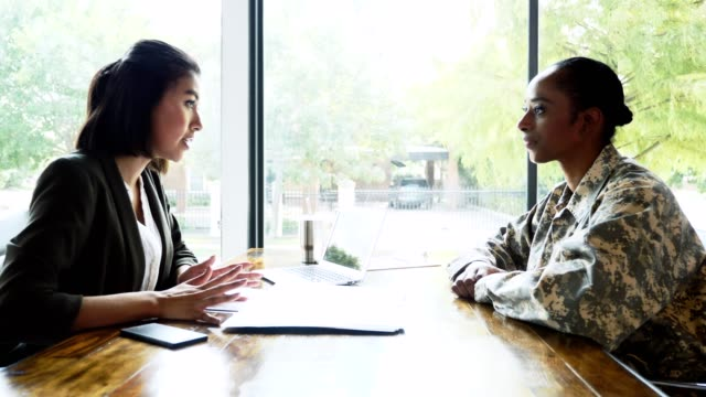 female soldier meets with bank loan officer - war veteran stock videos & royalty-free footage