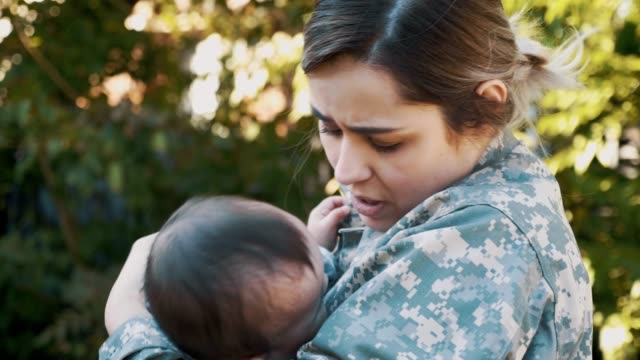 female soldier rocks her baby before leaving for military assignment - military stock videos & royalty-free footage