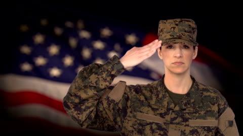 stockvideo's en b-roll-footage met vrouwelijke soldaat salute met ons vlag achtergrond - salueren