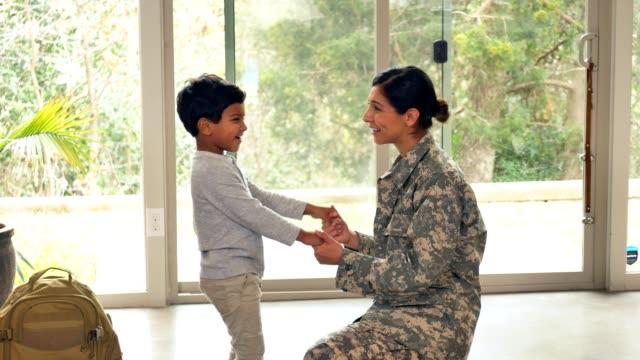 vídeos y material grabado en eventos de stock de soldado femenino habla con hijo pequeño antes de irse para la asignación - de descendencia mixta