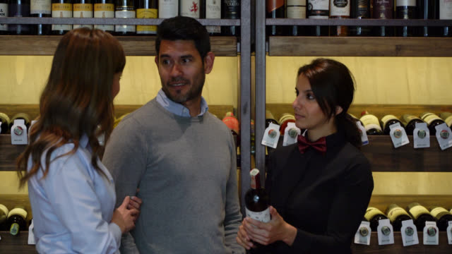 ワインセラーで顧客カップルに持っているワインボトルについて説明する女性ソムリエ - 説明する点の映像素材/bロール