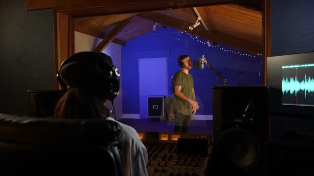 4K: Female Sound Engineer with Male Pop Singer in Recording Studio