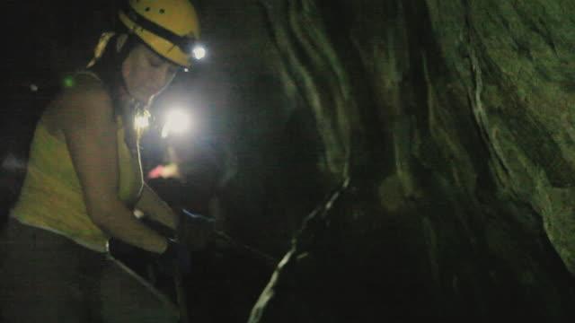 vidéos et rushes de ms la female spelunker descending narrow passage in cave using rope, yucatan, mexico - lampe frontale